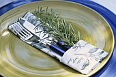 Place-setting with rosemary and herb-patterned fabric napkin