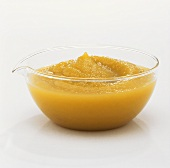 Apple puree in glass dish against white background