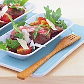 Slices of steak on rocket and cherry tomatoes