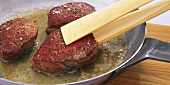 Frying fillet steaks in butter in a frying pan