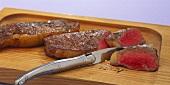 Fried sirloin steaks on wooden board