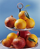 Citrus fruit and pomegranates on tiered stand