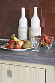 Fruit bowls and bottles in decorative holders