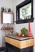 Blick in Küchenecke mit Rolltürschränkchen & rustikaler Ablage aus Holz unter Fenster mit schwarzem Festerrahmen