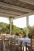 Holztische & Holzstühle auf überdachter Terrasse eines Restaurants