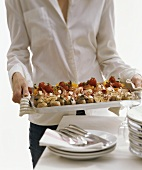 Woman serving a tray of prawn skewers and grilled vegetables