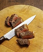 Sliced roast beef on wooden board with knife