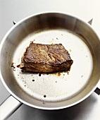 Fried beefsteak in frying pan