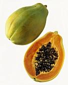 Whole papaya and half a papaya against white background