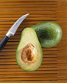 Whole avocado and half an avocado with knife