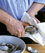Man taking the oyster meat out of an opened oyster