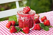 Cold stirred strawberry jam in a jar on a garden table