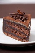 A slice of chocolate cake with chocolate flakes