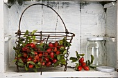 Rosehips in a basket and an empty jam jar