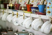 Porcelain cups hanging on a wall shelf in a kitchen