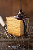 Baumkuchen (German layer cake) being prepared: covering the finished cake with chocolate glaze