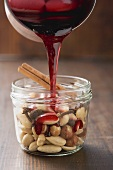 Red wine syrup being poured over nuts