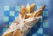 Baguettes in paper on a blue painted wooden surface