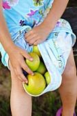 A girl holding green apples in her skirt