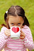 A girl drinking tea from a mug with a heart