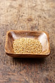 Mustard seeds in a wooden bowl