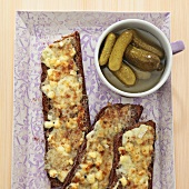 Toasted slices of bread with melted cheese and gherkins