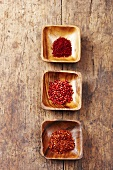 Chilli flakes, pink peppercorns and saffron threads in wooden bowls