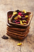 Dried rose petals in a stack of wooden bowls