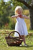 A blonde girl in a garden holding an apple