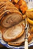 Sliced roast pork with a side of vegetables