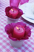 Candles in hollyhocks flowers as table decoration