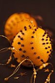 Christmas oranges pierced with cloves to hang as decoration