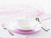 A place setting with a pink underplate and white plates