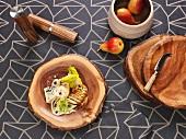 Holzbrettchen teils mit Essen dekoriert auf einer grauen gemusterten Tischdecke