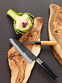 Half an artichoke and a knife on a wooden board