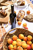 Fresh apricots, a bottle of wine, apricot cake and bread