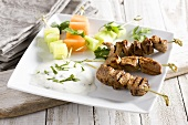 Lamb kebab with a yogurt dip and cucumber and melon kebabs