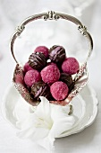 Various truffle pralines in a silver bowl decorated with flowers