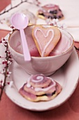 Heart-shaped biscuits with icing sugar and a sprig of almond flowers