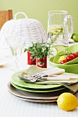 Plates, napkins, cutlery and a bouquet of herbs