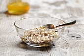 Muesli in a glass bowl with honey in the background