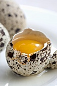 A cracked open quails' egg