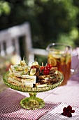 Various sandwiches on a table in a garden