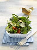 Spinach and rocket salad with strawberries and Parmesan in a paper dish