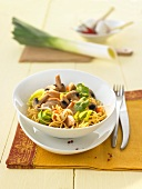 Wok-fried pasta with mushrooms, leek and chicken