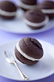 A chocolate whoopie pie on a plate (close-up)