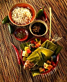 Gilt-head bream wrapped in a banana leaf with vegetables, rice and sauce (Indonesia)