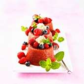 Three forest fruits puddings with cream and mint