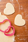 Unbaked, heart-shaped biscuits, biscuit dough and cutters