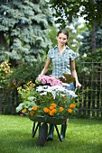 A young woman pushing a wheelbarrow full of flowers